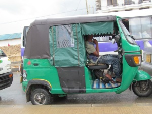 A bajaj, outfitted for the rainy season.  Usually the back, where the passengers sit, is open like the front.