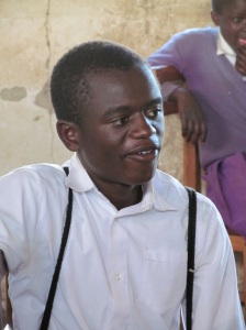 "This is Safari, another of my IID students.  He is such a bright kid and asks really good, smart questions and tries so hard but his English skills are below where they should be, again due to him receiving a substandard education in primary school.  He's a real sweetheart and sensitive and I think he got really frustrated last term because he started skipping school for weeks at a time.  I asked Vaselisa about him and she told me he would just go and sit in the forest instead of coming to school.  I thought I was misunderstanding her because of my Kiswahili but she laughed and said, ""Nope, he just goes and hangs out in the forest all day because he doesn't like to come to school.""  That made me sad so I told her to tell him that I thought he was a really smart kid and that he needed to come to school every day.  I think it worked because he started showing up regularly again (although it might not have been entirely my words that did it - Vaselisa's pretty tough so she might have just strong-armed him into coming).  He did well on the terminal exam so I'm optimistic but I worry he might slip between the cracks after I'm gone.  He's the classic example of the way the Tanzanian education system wastes intelligent minds because of their whole ""let's pretend that things are the way we want them to be and not actually deal with the reality of the way things are"" approach .  It is so frustrating."